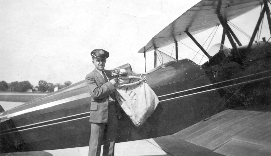 A pilot loading a plane with airmail, part of the history of airmail.