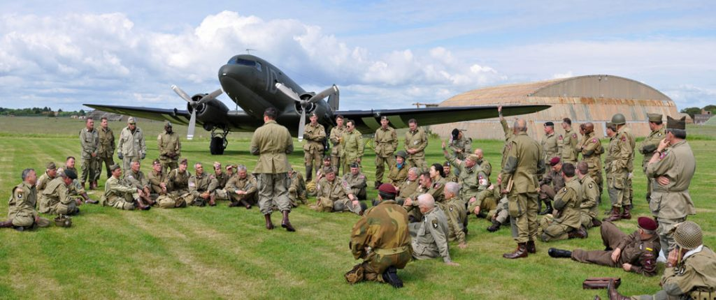 douglas dc-3 used in a d-day commemoration, surrounded by paratroops and soldiers