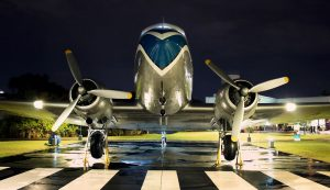 a douglas dc-3 at night on a wet runway