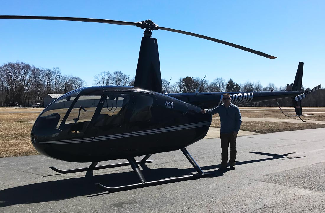Pilot working on helicopter rating posing with Robinson R44